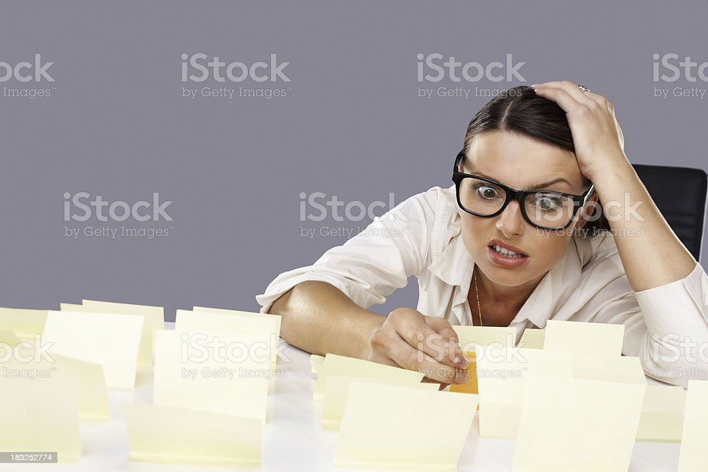 Stressed young business woman with notes stuck on her desk royalty-free stock photo