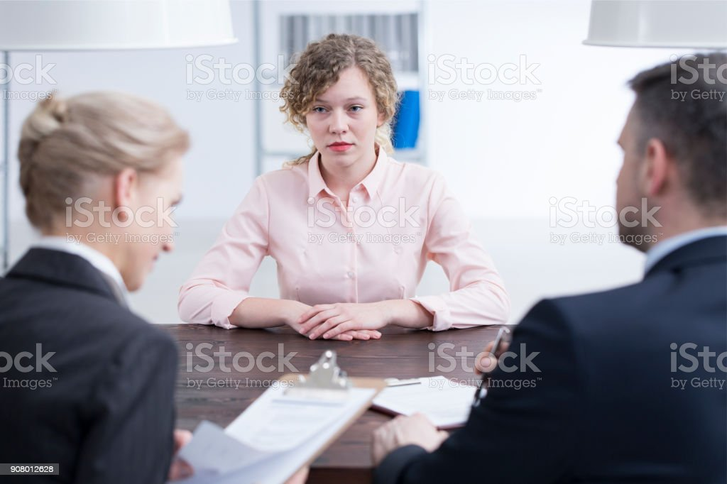 Stressed young girl and recruiters stock photo