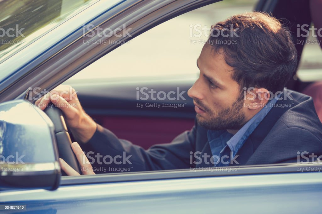 Stressed young man driver sitting inside his car stock photo