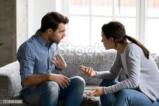 Stressed young married family couple arguing emotionally, blaming lecturing each other, sitting on couch. Depressed husband quarreling with wife, having serious relations communication problems.