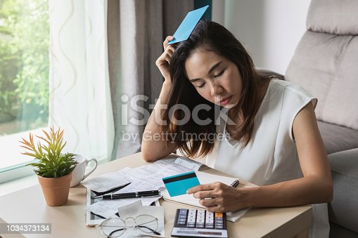 istock Stressed young woman checking bills, taxes, bank account balance and calculating expenses in the living room at home 1034373134