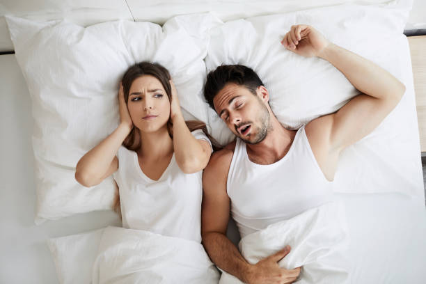 Stressed young woman covering her ears because her husband is snoring stock photo