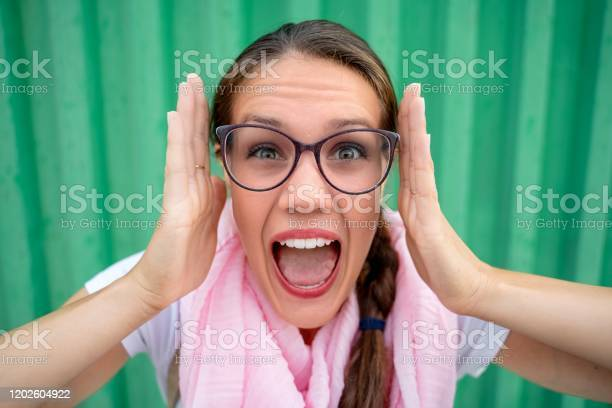 Stressed Young Woman Screaming And Looking At Camera Against Green Background Stock Photo Stock Photo - Download Image Now