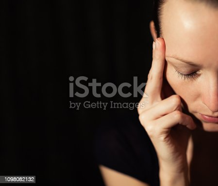 istock Stressed young woman sitting in the dark room 1098082132