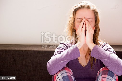 istock Stressed young woman sitting on couch 641732558