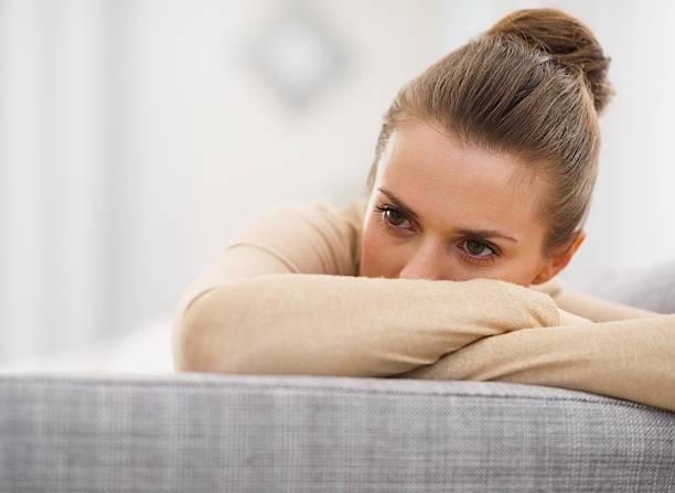 Gestresste Junge Frau sitzt auf sofa – Foto
