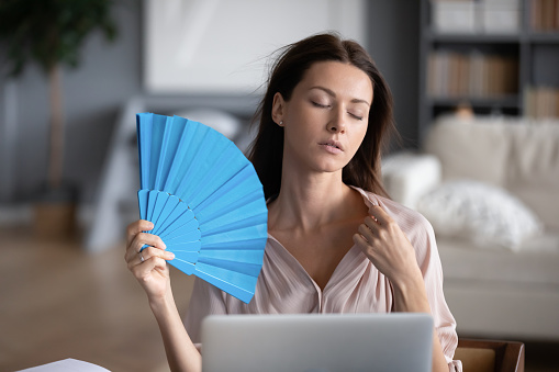 Stressed young woman use waver suffering from hot weather