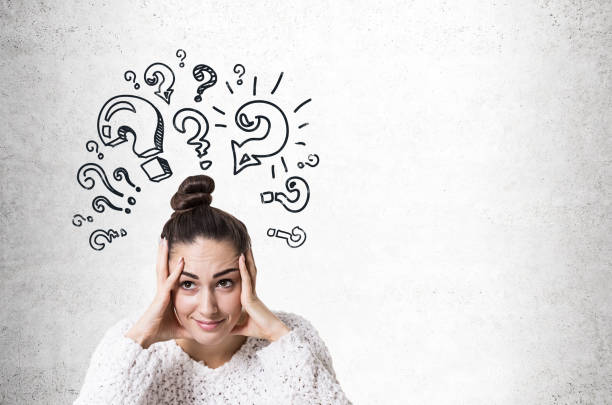 Stressed young woman with a bun, question marks stock photo