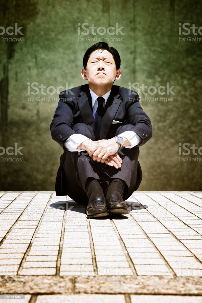 Stressed-out Japanese buisinessman sits and prays eyes closed stock photo