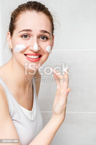 istock stressful beautiful woman applying moisturizing face cream for questioning skincare 650661466