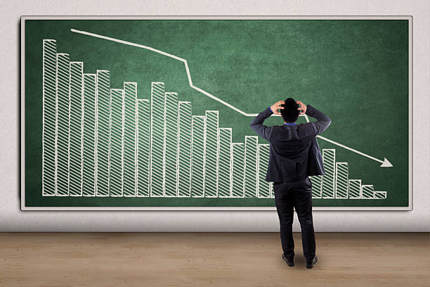 Stressful businessman looking at a declining graph stock photo