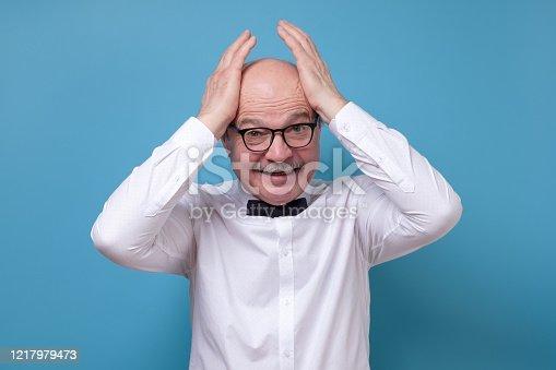 661896674 istock photo Stressful senior male screams in panic, keeps hands on head 1217979473