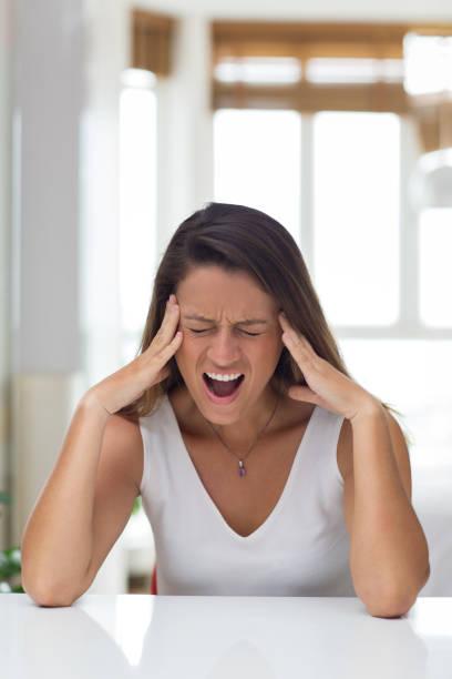 stressig junge frau, die weint vor schmerz - migräne vorbeugen stock-fotos und bilder