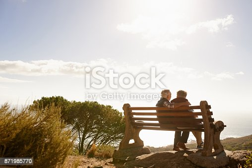 Young man listening to music on his smart phone and singing while woman sitting on the same park bench trying to use her phone