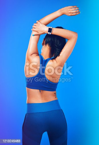 Rearview shot of a young sportswoman stretching her arms against a blue background