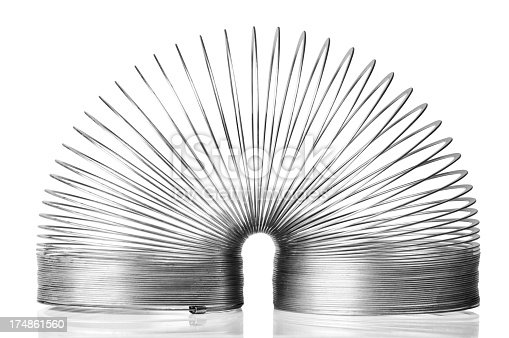 A child's metal slinky toy is isolated on a white background with a clipping path. The metal slinky is folded over in half, which is the position it is put into to start moving down stairs. It reflects into the shiny white background that it is sitting on.