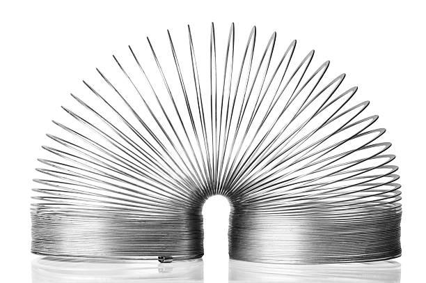 moving metal slinky juguete en posición sobre fondo blanco - hélice forma geométrica fotografías e imágenes de stock
