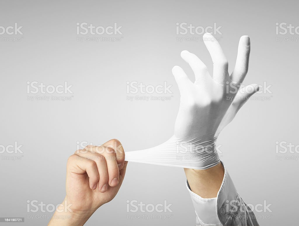 Stretching a white rubber glove over the left hand stock photo
