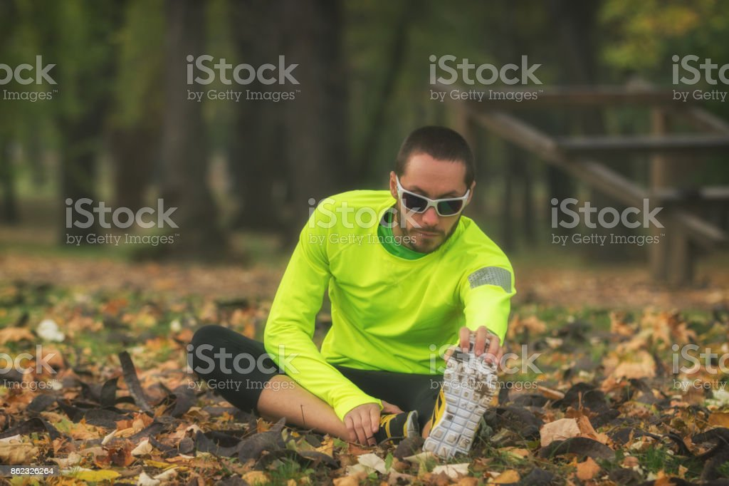 Stretching after / before exercising / jogging / running outdoors. stock photo