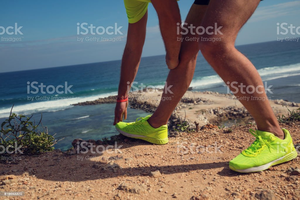 Stretching after jogging / exercise on the sea / ocean shore. stock photo
