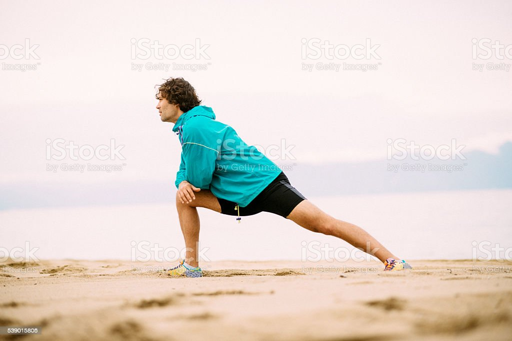 Stretching after training in summer on beach in sunset stock photo