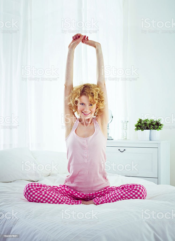 Stretching arms in the morning Happy young adult woman sitting cross-legged on a bed in the morning and stretching her arms,looking at camera and smiling. 20-24 Years Stock Photo