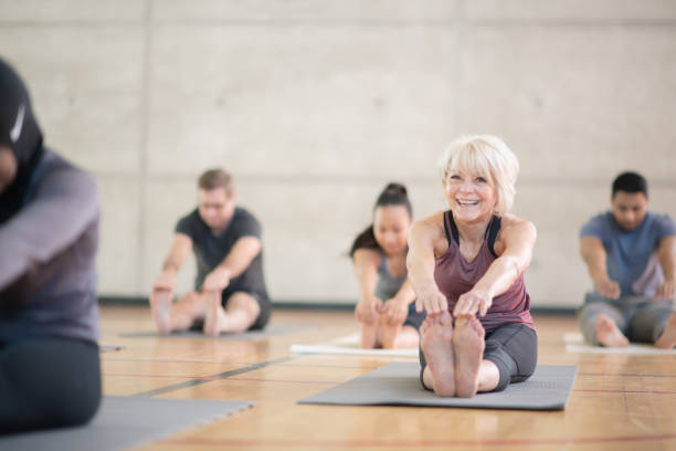 Stretching Class A group of diverse people are sitting on exercise mats and stretching to touch their toes. They are enjoying their afternoon as they focus on their health. yoga studio stock pictures, royalty-free photos & images