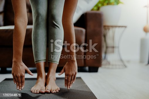 Closeup shot of an unrecognisable woman touching her toes while exercising at home