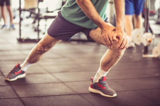 Stretching exercise. Senior man stretching and working exercise for legs. Close up. human leg stock pictures, royalty-free photos & images