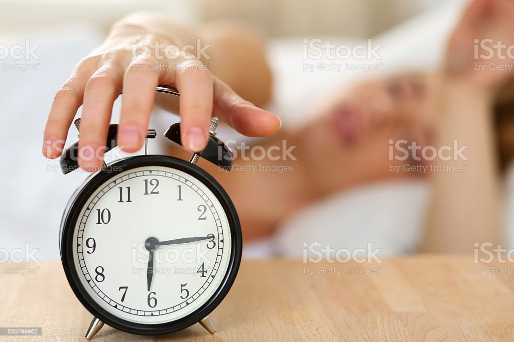 Stretching hand of sleepy young woman trying kill alarm clock stock photo
