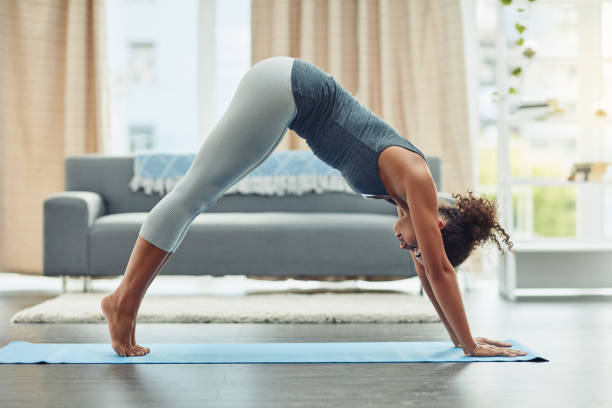 Stretching her slim body with yoga stock photo