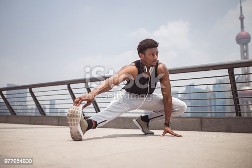 Young Man Stretching Before Running In City