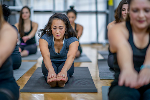 A multi-ethnic group of adult women are indoors at a health center. They are all wearing grey athletic clothing and stretching to touch their toes.