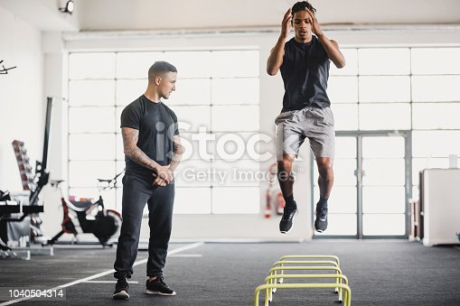 Young man having a personal training session in the gym. He is doing warm up exercises while his personal trainer guides him.