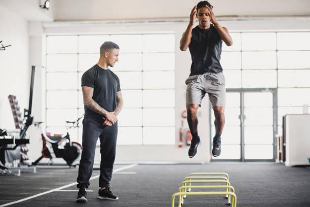 estiramientos en el gimnasio con un entrenador personal - entrenador personal fotografías e imágenes de stock