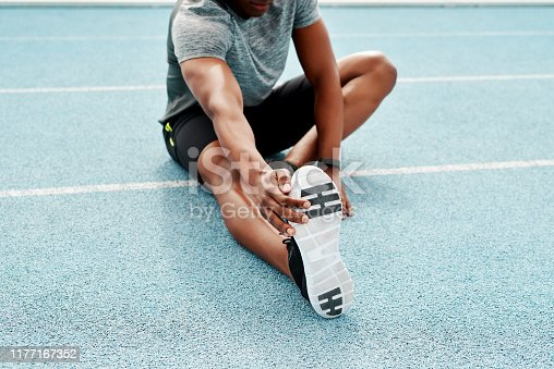 Cropped shot of an unrecognizable athlete sitting alone and stretching before a run on the track