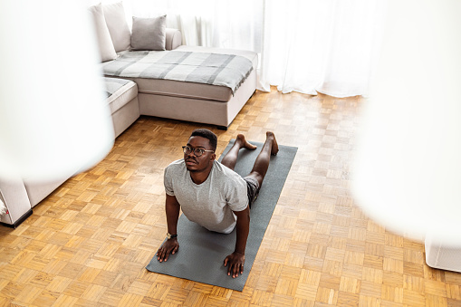 Young man in cobra yoga pose on exercise mat doing stretching exercise in his living room during Covid-19 pandemic lockdown.