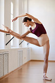 Serious graceful young woman with hair bun wearing pointe shoes stretching leg and body using barre in ballet school