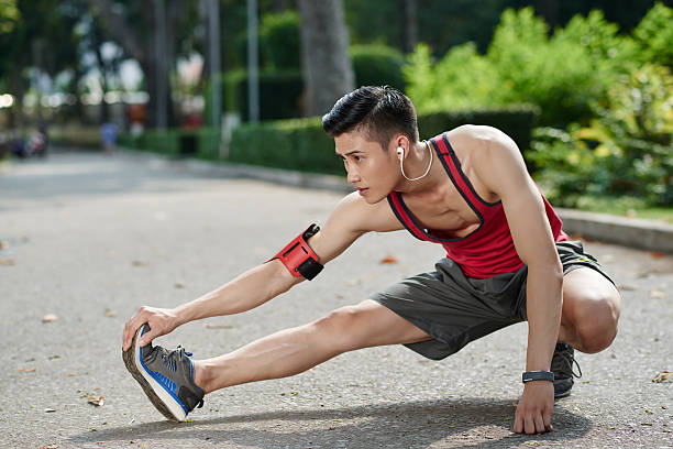 Stretching legs Asian young jogger stretching his legs outdoors hamstring stock pictures, royalty-free photos & images