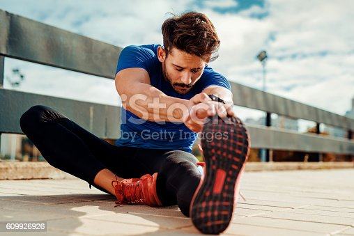 Young male jogger athlete training and doing workout outdoors in city