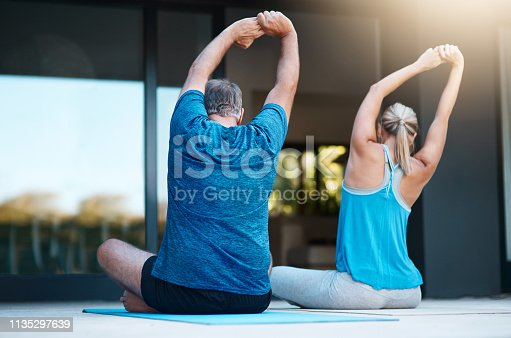 Rearview shot of a mature couple stretching before they start their yoga exercises outside of their home