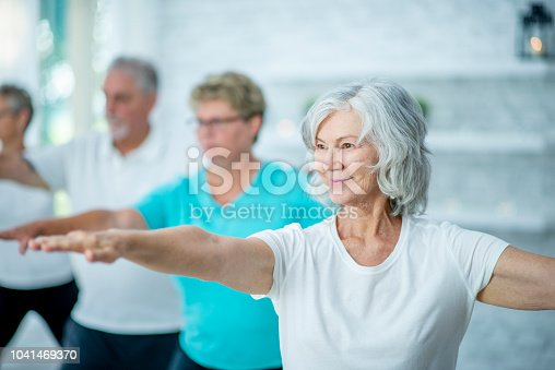 A group of seniors are doing tai chi in a fitness center. They are stretching their arms outwards to do a pose.