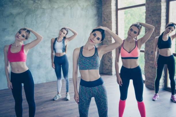 dehnen der hals damen. fünf junge modische sportlerinnen sind ausbildung, so biegsam und flexibel, trendige sport-outfit tragen, schuhe, im modernen studio - hals übungen stock-fotos und bilder