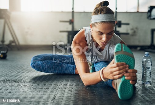 Shot of a young attractive woman stretching in a gym