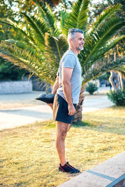 dehnung der muskeln müde beine - bein tag routine stock-fotos und bilder
