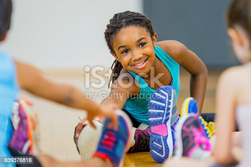 A young African American girl leads a stretch during gym class as part of their yoga routine.