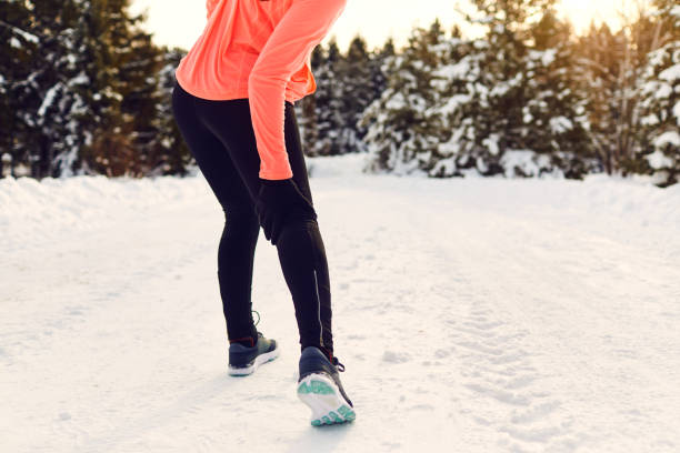 Stretching, trauma, pain of the legs when running in winter. stock photo