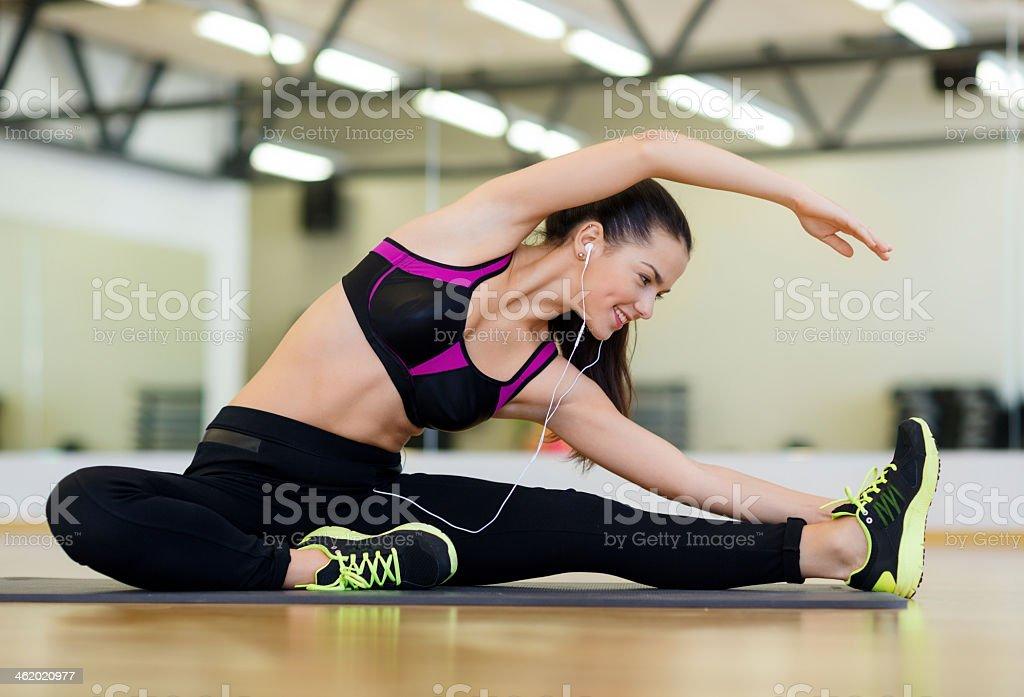 Estiramiento mujer joven con auriculares en el gimnasio - Foto de stock de Actividades y técnicas de relajación libre de derechos