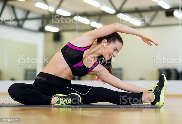 Estiramiento Mujer Joven Con Auriculares En El Gimnasio Foto de stock y más banco de imágenes de Actividades y técnicas de relajación