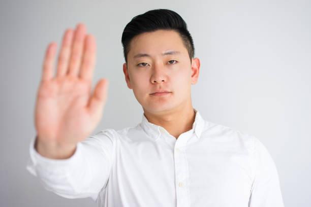 strenge asiatische mann zeigt stop geste - wortarten bestimmen übungen stock-fotos und bilder